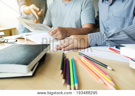 Education teaching learning and people concept. Group of high school students or classmates with helps friend catching up workbook learning in classroom Tutor book with friends.