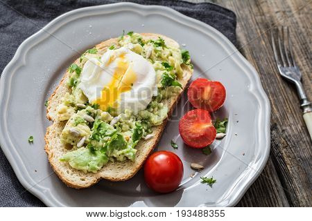 Poached egg on avocado toast. Delicious and healthy snack: mashed avocado with cilantro and sunflower seeds on toasted sourdough bread topped with poached egg on a gray plate. Closeup view