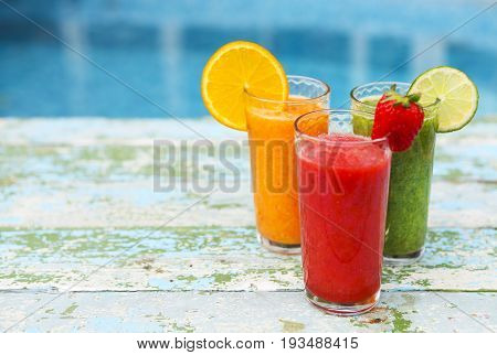 Assortment of fruit and vegetables smoothies in glass on white wooden background. Fresh organic Smoothie. Superfoods and health or detox diet food concept.