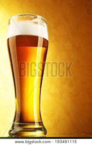 Glass of beer on a golden background