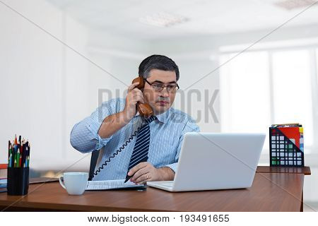 Businessman working in the office. The supervisor gives orders to the subordinates by phone. Rapid adjustment. Looks at the monitor screen.