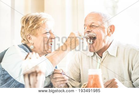 Happy retired senior couple in love enjoying bio icecream cup - Joyful elderly lifestyle concept - Wife feeding husband and having fun at bar cafe restaurant during evergreen vacation - Retro filter