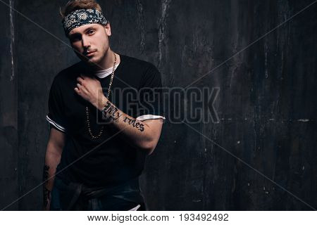 Dangerous tattooed gang member man stay on dark background. American gangster, dangerous people, urban style concept