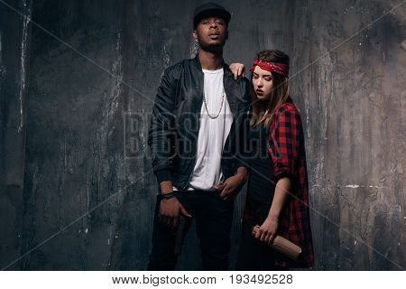 Gang members couple with gun and bottle. Criminal teenagers on dark background. Love and romance in addicted family