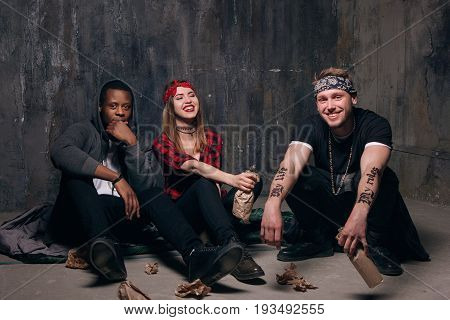 Group of alcoholic young people students party. Youth addiction problem. Laughing drunk caucasian girl holding alcohol bottle, smiling guys with tattoo sits near .