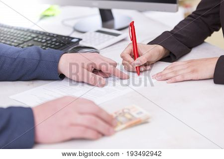 Busineswoman signing loan contractwith money Euro banknotes on the table