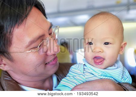 Happy asian father and child sitting together in airplane cabin near window Baby's First Flight ( Kid's First Time On An Airplane) Traveling with a newborn concept / Shallow depth of field