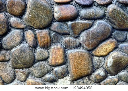 Stone texture of convex cobblestones in the foundation of the building