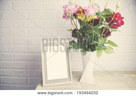 rose on vase and photo from in brick wall background
