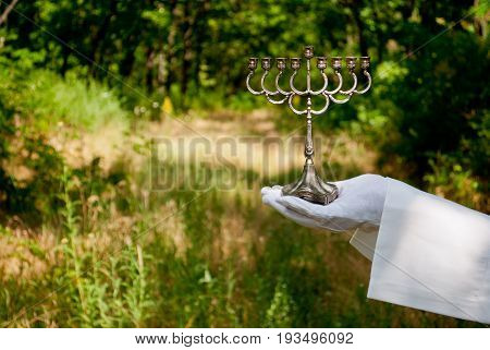 A waiter's hand in a white glove and a white napkin holds a metal candlestick a Jewish candlestick on a blurred background of nature green bushes and trees
