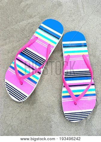 Colorful flip-flops on a sandy beach of a sea