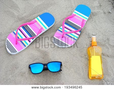 Flip-flops, sunglassess and sun-care milk on a sandy beach