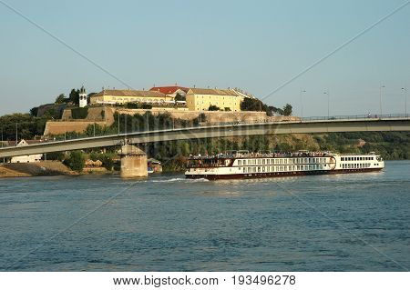 Novi Sad Serbia - July 27 2008: Tourist ship full of tourists sails under the bridge on the Danube river on late afternoon near the Petrovaradin Fortress and the city of Novi Sad.