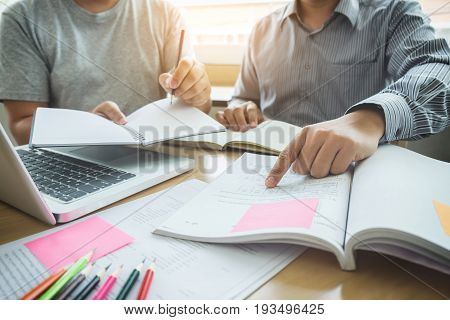 Education teaching learning technology and people concept. Two high school students or classmates with helps friend catching up workbook learning in classroom Tutor book with friends.