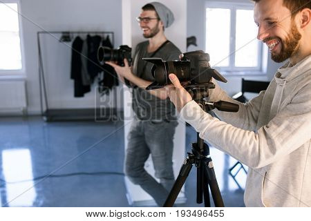Two laughing professional photographers taking shots in studio. Happy moments at work, joke, have a good time concept