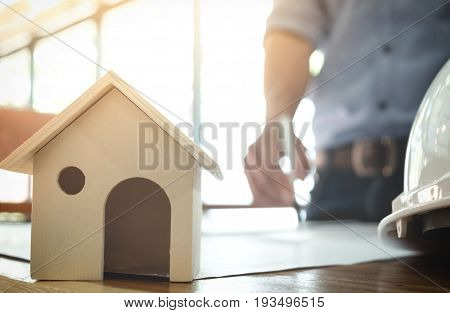 Image of engineer or architectural project Close up of small house model and architects engineering working on blueprint with engineering equipment tool blurred background.