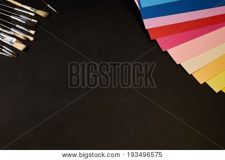 Multicolour sheets of paper and brushes with copy space on black
