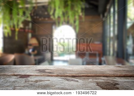 Selected focus empty old wooden table and coffee shop cafe or restaurant blur background image. for your photomontage or product display.