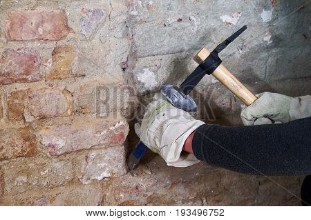 Two hands with hammer and chisel working on brick wall