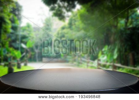 Selected focus empty black wooden table and green garden or forest blur background with bokeh image. for your photomontage or product display.