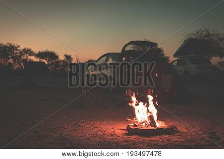 Burning camp fire at dusk in camping site Botswana Africa. Summer adventures and exploration in the african National Parks. Selective focus on fire cars and tents out of focus in the background. Toned image.