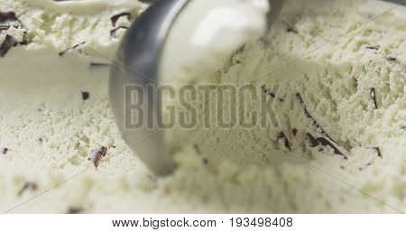 macro mint ice cream with chocolate chips being scooped, wide photo