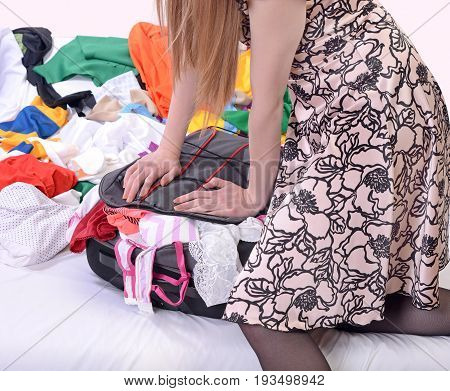 Girl collects things in a suitcase on a long trip. Fees on vacation