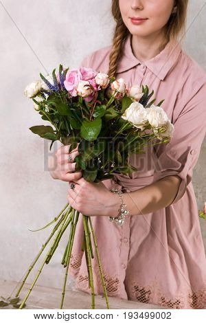 Florist makes a bouquet of rose flowers. The decorator works in a greenhouse with a pink bouquet. Floristic workshop, skill, decor, small business concept