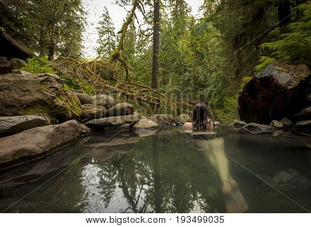 Young caucasian woman looking out from natural hot spring.