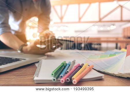 Color samples colour chart swatch sample Graphic designer being selecting Color table and graphics tablet pen at workplace with work example in camera and laptop on wooden desk.