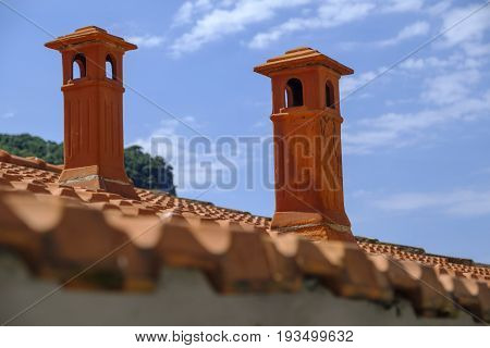 Beautiful red terracotta chimneys on a tiled rooftop in Portovenere Italy against blue sky