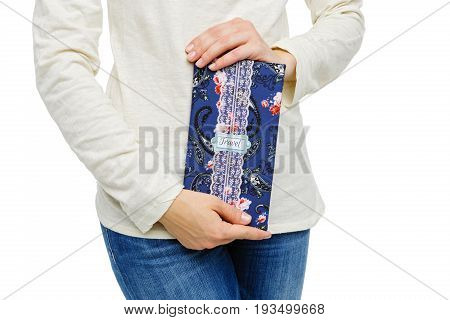 young woman in jeans holding beautiful handmade scrapbooking travel paper folder. Isolated on white background. Copy space.