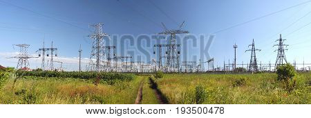 Panorama of high voltage substation. Distribution electrical power. Ukrainian oblenergo sale. Silhouettes of pylons and towers.