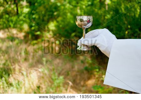 A waiter's hand in a white glove and a white napkin holds a metallic glass with a carving pattern on a blurred background of nature green bushes and trees