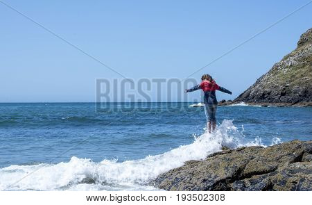 Young girl in wind breaker standing on rock with waves crashing over her feet.