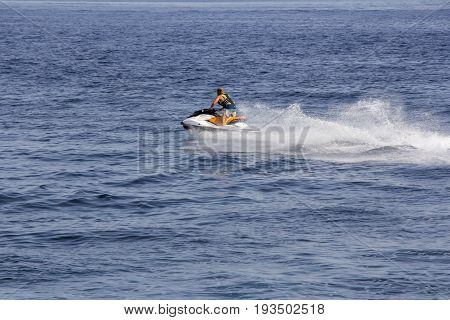 The young Man riding jet ski in blue sea