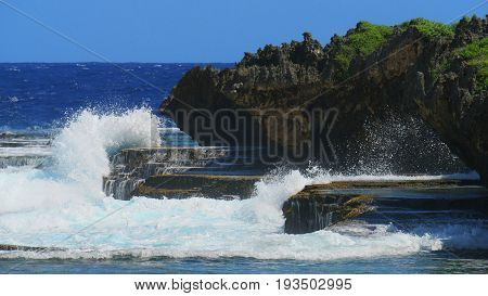 Picturesque cliffs and huge waves  Foaming waves crashing against beautiful cliffs and stones at a tropical beach
