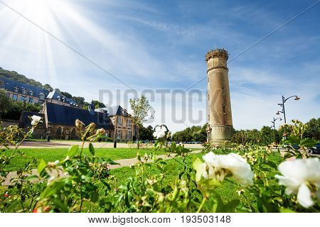 Beautiful view of Honfleur streets with old lighthouse at sunny day, Normandy, France, Europe