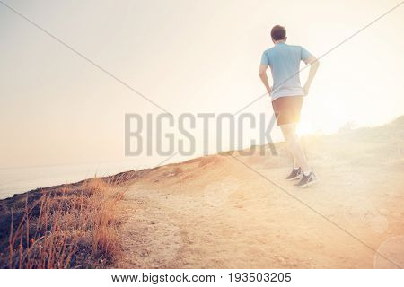 Male Jogger Sprinting Outdoors. Fit Young Sport Fitness Model Outdoor. Exercising Fitness and Healthy Lifestyle Back view