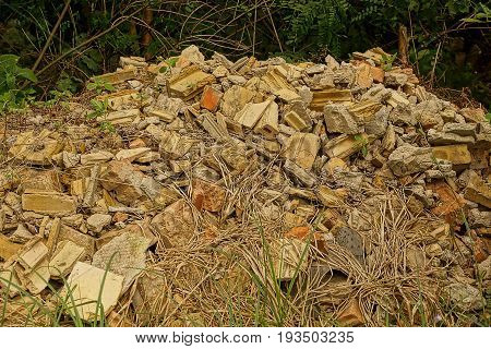 Building debris from broken bricks and tiles in the bushes