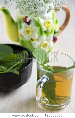 Nettle tea on the wood background leaves in the cup and wild flowers in a ceramic kettle