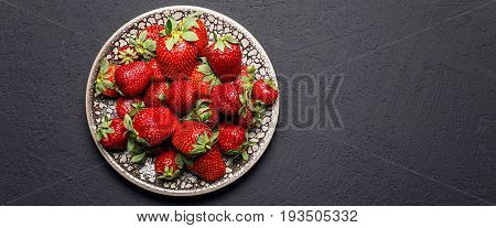 fresh ripe useful fruit strawberry in a clay bowl closeup on a black background, border design panoramic banner