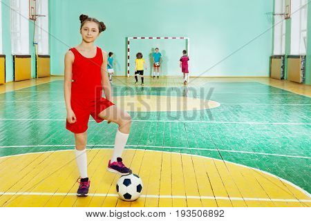 Portrait of sporty preteen girl, football player, putting her foot on ball in sports hall