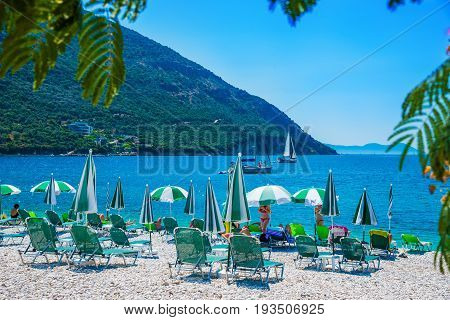 Chairs and umbrellas on the famous beach of Lefkada Poros Mikros Gialos in summer holiday, Greece