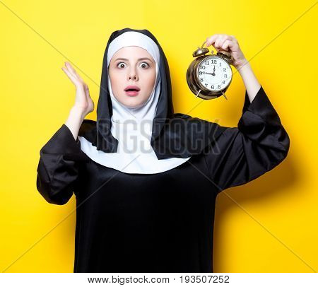 Young Surprised Nun With Alarm Clock