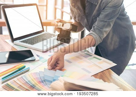 Color samples colour chart swatch sample Graphic designer being selecting Color band and graphics tablet pen at workplace with work example in camera and laptop on wooden desk.