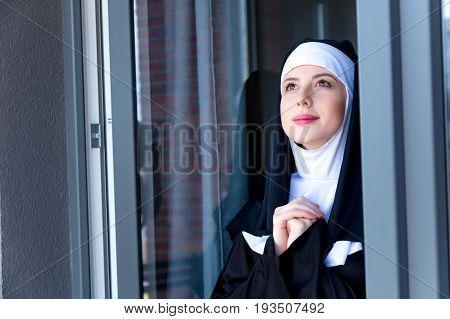 Young Smiling Nun Near Window