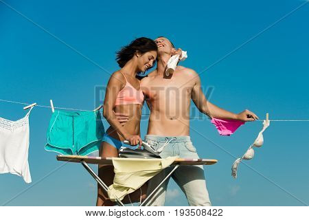 family. young happy couple in love of woman with buttocks and muscular athletic man at iron ironing board with clothesline rope with underwear on sunny blue sky background household and summer