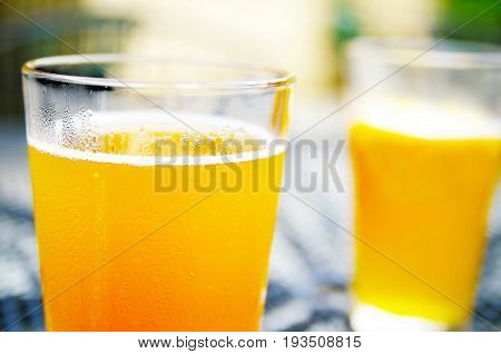 Two pints of unfiltered wheat beer at an outdoor cafe
