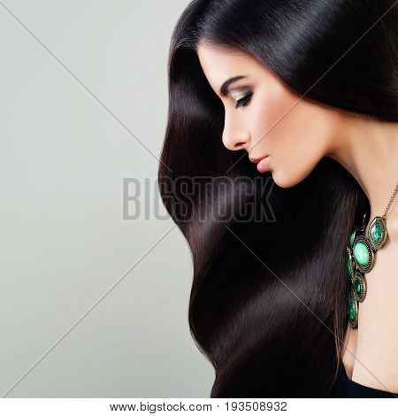 Haircare Concept. Glamorous Brunette Woman with Perfect Hairstyle and Makeup. Beautiful Model with Long Healthy Hair Profile